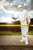 Technician in sterile suit behind barrier tape Stock Image
