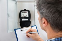 Technician taking reading of electric meter. Technician Writing Reading Of Meter On Clipboard Royalty Free Stock Photography