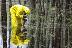 Technician taking sample of water to container in floods contaminated area. Technician in fully protective overalls taking sample of water to container in floods royalty free stock image