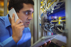 Technician talking on mobile phone while analyzing server. In server room Royalty Free Stock Image