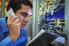 Technician talking on mobile phone while analyzing server. In server room Stock Photo