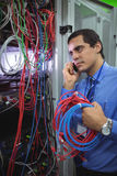 Technician talking on mobile phone while checking cables. In a rack mounted server Stock Photos