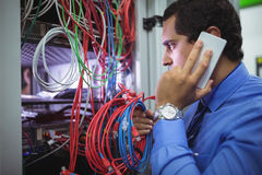 Technician talking on mobile phone while checking cables. In a rack mounted server Royalty Free Stock Image