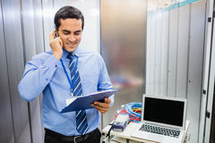 Technician talking on mobile phone. Technician dictating checklist report on mobile phone in server room Stock Image