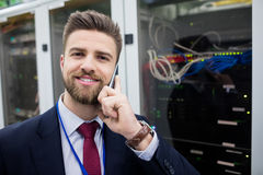 Technician talking on mobile phone. Portrait of technician talking on mobile phone in server room Royalty Free Stock Photography