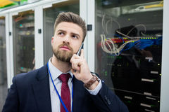 Technician talking on mobile phone. In server room Stock Photos