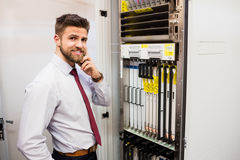 Technician talking on mobile phone in server room. Portrait of technician talking on mobile phone while working in server room Royalty Free Stock Image