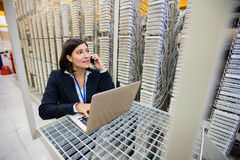 Technician talking on mobile phone in server room Royalty Free Stock Image