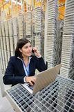 Technician talking on mobile phone in server room Stock Image