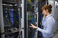 Technician talking on phone while analysing server Stock Photo