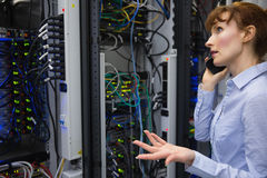 Technician talking on phone while analysing server Royalty Free Stock Photos