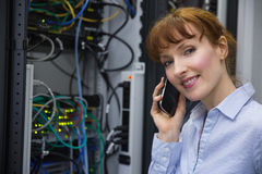 Technician talking on phone while analysing server Stock Photography