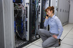Technician talking on phone while analysing server Royalty Free Stock Image