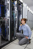 Technician talking on phone while analysing server Royalty Free Stock Photo