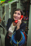 Technician talking on phone while analyzing server Royalty Free Stock Image