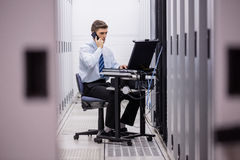 Technician talking on phone while diagnosing servers. In large data center Stock Images