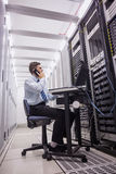 Technician talking on phone while looking servers Royalty Free Stock Photography