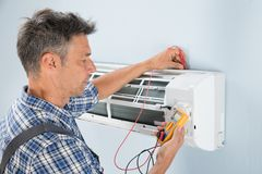 Technician testing air conditioner. Portrait Of A Mid-adult Male Technician Testing Air Conditioner With Digital Multimeter Stock Photography