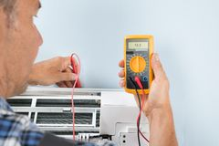 Technician testing air conditioner. Portrait Of A Mid-adult Male Technician Testing Air Conditioner With Digital Multimeter Royalty Free Stock Photos