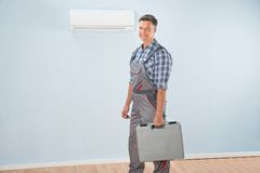 Technician with toolkit. Photo Of Air Conditioner Repairman With Toolkit Royalty Free Stock Photos