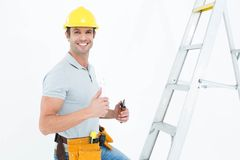 Technician with tools showing thumbs up by step ladder Stock Photos