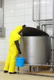 Technician in uniform with  bucket at industrial tank Royalty Free Stock Photo