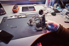 Technician uses a magnifying glass to carefully inspect the internal parts of the smartphone in a modern repair shop. The technician uses a magnifying glass to royalty free stock photo