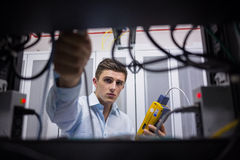 Technician using cable tester while fixing server Royalty Free Stock Images