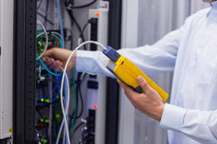 Technician using digital cable analyser on servers. In a large data center Royalty Free Stock Photos
