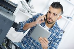 Technician using phone and laptop tablet. Technician using his phone and laptop tablet Stock Photos