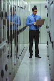 Technician using laptop while analyzing server. In server room Stock Photos