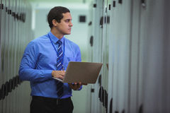 Technician using laptop while analyzing server. In server room Royalty Free Stock Photos
