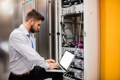 Technician using laptop while analyzing server Stock Photography