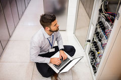 Technician using laptop while analyzing server. In server room Stock Photography