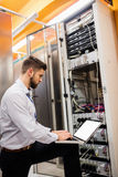 Technician using laptop while analyzing server. In server room Stock Image