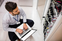 Technician using laptop while analyzing server Stock Image