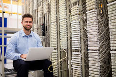 Technician using laptop while analyzing server. In server room Royalty Free Stock Images