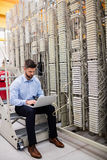 Technician using laptop while analyzing server. In server room Royalty Free Stock Image