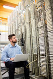 Technician using laptop while analyzing server. In server room Royalty Free Stock Photo