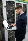 Technician using laptop while analyzing server. In server room Stock Images