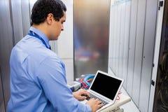 Technician using laptop. Focused technician using laptop in server room Stock Photos
