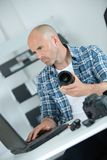 Technician using laptop and holding camera lens. Technician Stock Photography