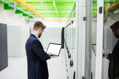 Technician using laptop. In server room Royalty Free Stock Photos