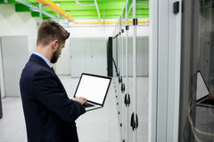 Technician using laptop. In server room Stock Photography