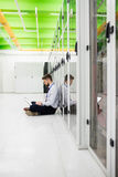 Technician using laptop. In server room Royalty Free Stock Photo