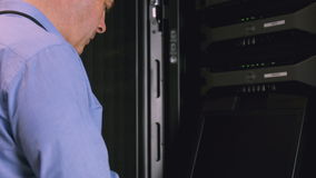 Technician using laptop to analyse server stock video