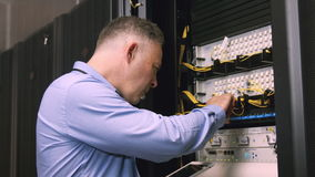 Technician using laptop to analyse server stock video footage