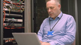 Technician using laptop to analyse server stock footage