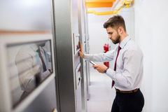 Technician using mobile phone. In server room Royalty Free Stock Images