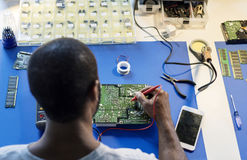 Technician using multimeter with computer electronics parts Stock Photography